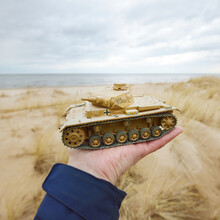 German WWII Panzer III Scale Model Toy Tank In A Hand Close-up. Sand Dunes Of The Baltic Sea In The Background. Modeling, Collecting, Education, History Concepts