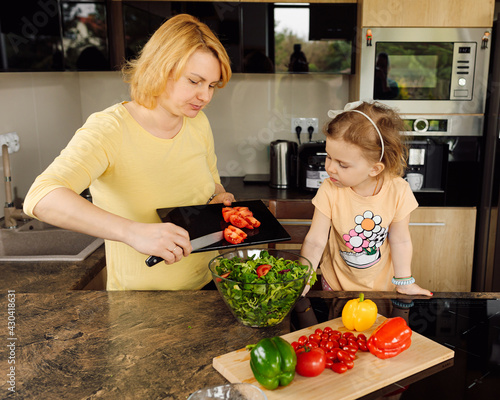 Photo Happy mom and daughter little girl are happy to spend time together cooking fresh vegetable salad