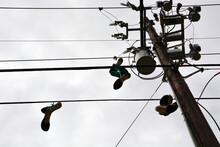 Several Pairs Of Old Running Shoes Dangle From The Power Lines