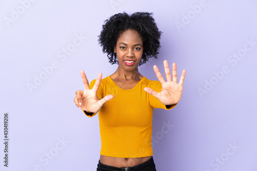 Young African American woman isolated on purple background counting eight with f Fototapeta