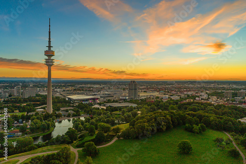 Canvas Summer sunrise over the beautiful bavarian city of Munich with its popular and eyecatching sightseeing view over the Olympic park with the high tower under orange colored sky in the morning