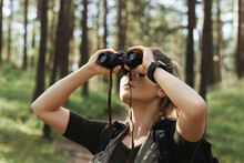 Female Hiker Is Using Binoculars For Bird Watching In Green Forest