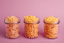 Three Glass Jars With Variety Of Uncooked Golden Wheat Pasta On Minimal Pink Background Angle View