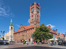 Torun, Poland. Old Town Market Square With Nicolaus Copernicus Monument In Front Of The Old Town Hall, And Church Of The Holy Spirit In The Background. The Monument Was Erected In 1853.