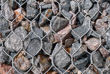Stones And Pebbles In Wire Mesh Background. Rockfall Protection Barrier. Gabion Wall Construction Using Steel Wire Mesh Basket. Modern Wall Construction.