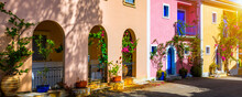 Traditional Street With Greek Houses With Flowers In Assos, Kefalonia Island. Traditional Colorful Greek Houses In Assos Village. Blooming Fuchsia Plant Flowers. Kefalonia Island, Greece