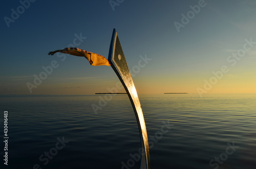Canvas Print Closeup of a ship's wooden prow taken off and used as a flag pole on a tropical