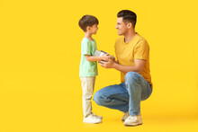 Little Boy Greeting His Dad On Father's Day Against Color Background