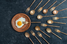 Ceramic Plate With Fried Egg And Brass Forks And Spoons Look Like Sperm Competition. Spermatozoons Floating To Ovule