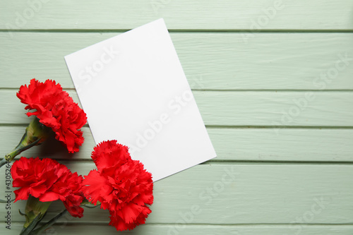 Fresh carnation flowers with empty paper sheet on color wooden background - fototapety na wymiar