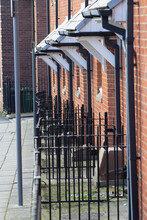 City Railings Next To The Street With Roofs And Gutters