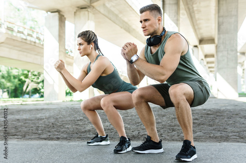 Athletic couple doing squats during street workout - fototapety na wymiar