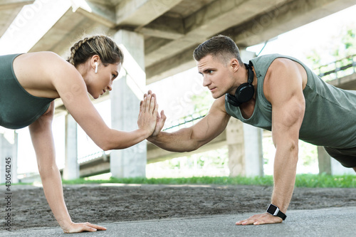 Athletic couple and fitness training outdoors. Man and woman doing push-ups exercise. - fototapety na wymiar
