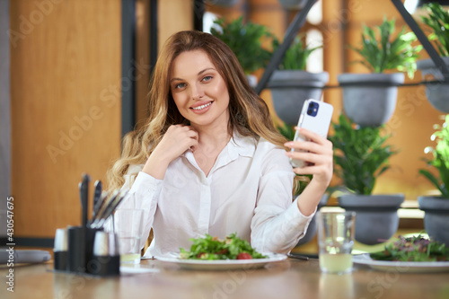 Front view of smiling attractive woman in white shirt eating tasty salad and doing selfie on modern phone. Concept of talking with people online in telephone.  - fototapety na wymiar