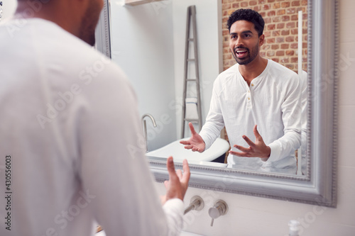 Man At Home Practising Giving Speech Or Presentation In Bathroom Mirror