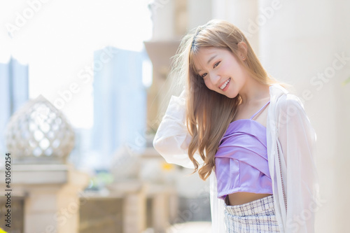 Obraz na plátně Asian beautiful lady who has bronze hair smiles and walks on the street in fashion style theme