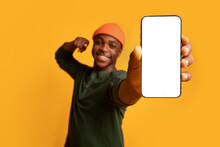 Cheerful Black Guy Pointing On Smartphone With White Screen In His Hands