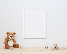 Neutral Nursery Frame Mockup Hanging On Wall, White Vertical Frame Mock Up For Wall Art, Soft Toy Bear, Wooden Blocks On Shelf.