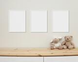 3 blank vertical frames mockup on wall for nursery wall art display, baby room three white frames mock up, wooden shelf, soft toys on shelf.