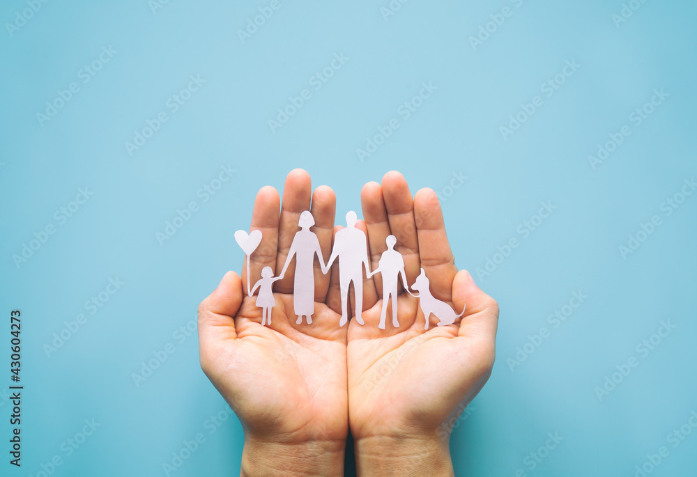 Obraz Hand holding family paper cut on blue background. Family day concept, foster care, domestic violence, homeschool, international day of families, world mental health day, world autism awareness day. fototapeta, plakat