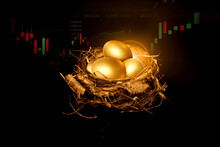 The Golden Eggs Are Placed In The Nest On The Background Of The Stock Market.