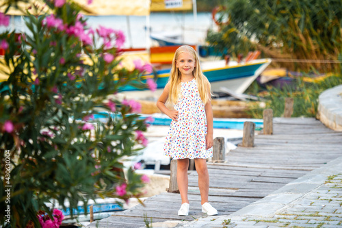 Canvas Print A little girl on the embankment by the river in a white sundress in the city of Dalyan