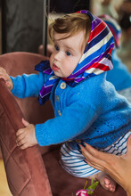 Cute Blue-eyed Toddler Girl In A Blue Sweater And Headscarf. It Stands On A Soft Chair. Indoor.