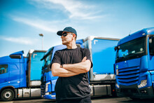 Professional Truck Driver With Hat And Sunglasses Confidently Standing In Front Of Big And Modern Truck Blue Truck Fleet. Bright Sunny Day. People And Transportation Concept.