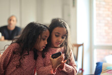 Two Young Sisters Use A Smartphone