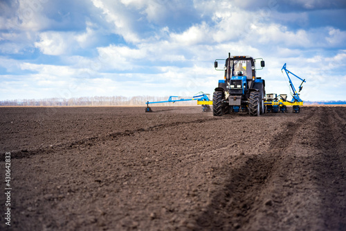 Obraz na plátně sowing work in the field in spring. Tractor with seeder