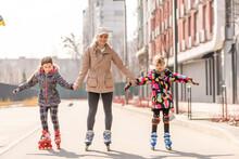 Family Rollerskating In Park. Active Walk. Preschool Girl Having Active Walk With Her Mother