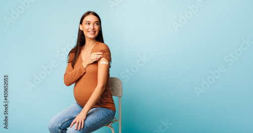 Fototapeta Vaccinated Pregnant Woman Showing Arm After Vaccine Injection, Blue Background obraz