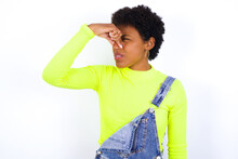 Displeased Young African American Woman With Short Hair Wearing Denim Overall Against White Wall Plugs Nose As Smells Something Stink And Unpleasant, Feels Aversion, Hates Disgusting Scent.