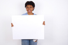 Happy African American Female With Afro Hair Wears Jeans Overalls Over White Wall Holding Empty Paper Board Advertising Offer Text Standing. Autumn Advertisement Banner.