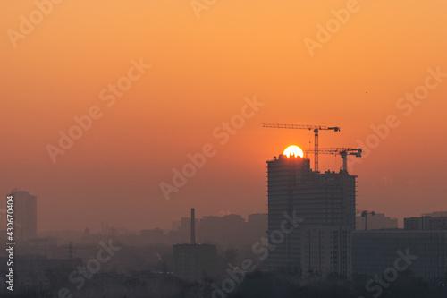 Obraz Warszawa zachód słońca Wola żuraw wieżowy budowa - fototapety do salonu