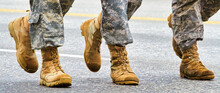 Close Up Boots On The Ground Marching. Army Boots Made Of Brown Leather. Dirty And Worn