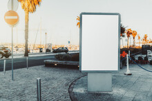 A Vertical Blank Ad Poster Mockup On The Sidewalk Near The Seaside; An Empty Street Advertising Billboard Template On Embankments; A White Advert Banner Mock-up Placeholder In Urban Settings