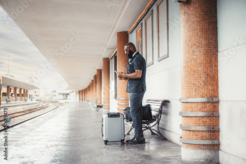 A pensive dapper bearded bald African man entrepreneur has missed his train and now watching train schedule on a smartphone while standing on a railway station depot platform with two bags of baggage