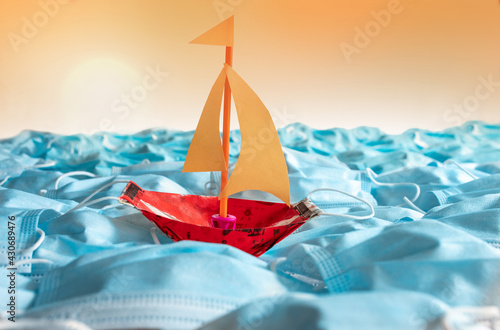 Sailing boat on open sea created of surgical masks - fototapety na wymiar