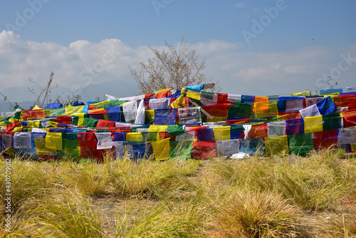 Fotografia Closeup of the colorful handkerchiefs hanging from the ropes on the grassy field