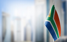 A Small Flag Of South Africa On The Background Of A Blurred Background