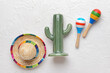 Leinwandbild Motiv Cactus, maracas and sombrero hat on light background