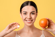 Beautiful Woman With Grapefruit And Vitamin C Pill On Color Background