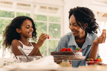 Girl Assisting Mother In Baking A Cake In Kitchen