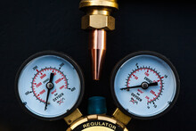The Upper Part Of The Torch With A Copper Tip And The Pressure Regulator Of The Oxygen Cylinder With Monometers On A Black Background, Top View.