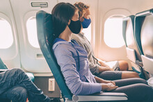 Couple Tourists Wearing Face Masks On Travel Vacation Flight Inside Plane. Coronavirus Safety Prevention For Passengers Of Flight. People Lifestyle.