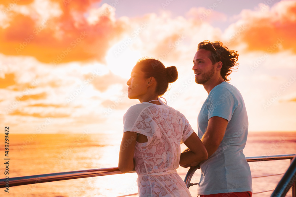 Obraz Sunset cruise romantic couple watching view from boat deck on travel vacation. Silhouette of man and woman tourists relaxing on outdoor balcony of ship. fototapeta, plakat