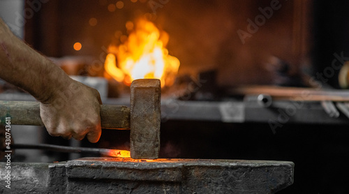 Fotografia Blacksmith working metal detail with hammer on the anvil in rustic forge