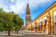 Cordoba, Spain. View Of Torre Campanario - Historical Bell Tower And Courtyard Planted With Orange Trees