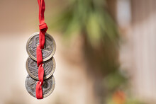 Chinese Coins Hanging From Red Ribbon. Selective Focus. Copy Space